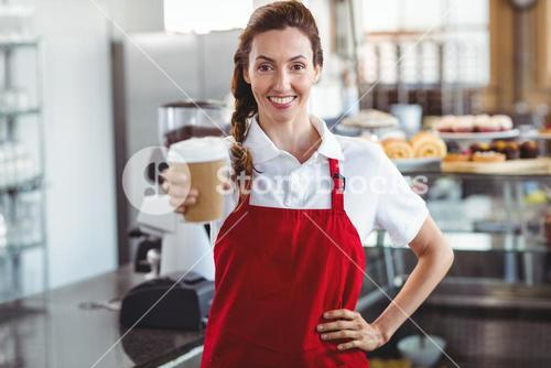 Pretty barista giving take-away cup