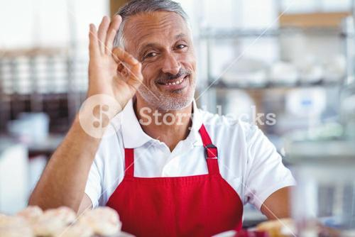 Happy barista looking at camera and gesturing ok sign