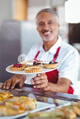 Barista holding a plate of pastries