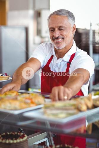 Barista putting plates of pastries on counter