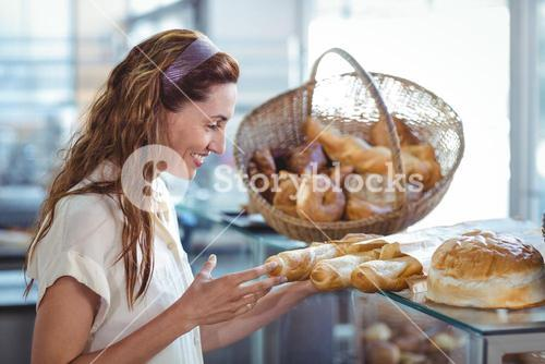 Pretty brunette pointing at loaf of bread