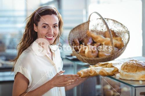 Pretty brunette smiling at camera and holding loaf of bread