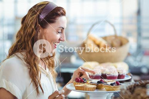 Astonished pretty woman pointing at cakes