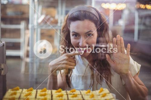 Pretty brunette looking at camera through the glass with finger in the mouth