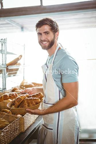 happy worker holding a basket of croissant
