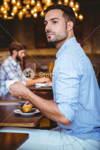 Curious businessman holding a cup of coffee