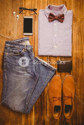 Shirt shoes jean glasses next to wallet and smartphone