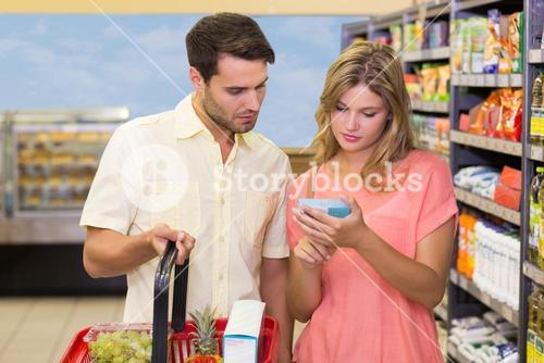 A bright couple buying products using shopping basket