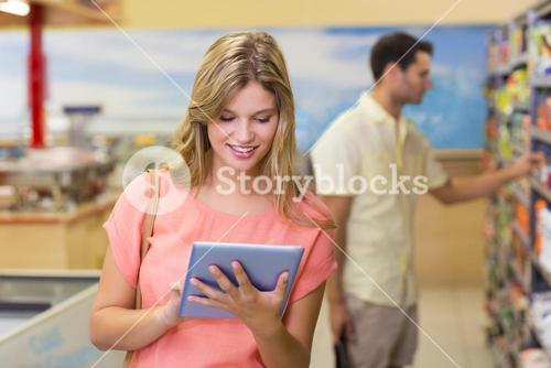 Smiling pretty blonde woman using digital tablet and buying products