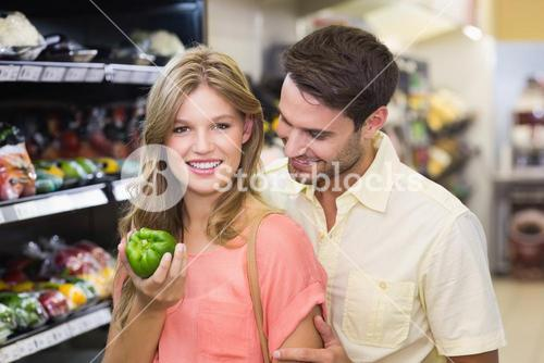 Portrait of smiling bright couple buying food products