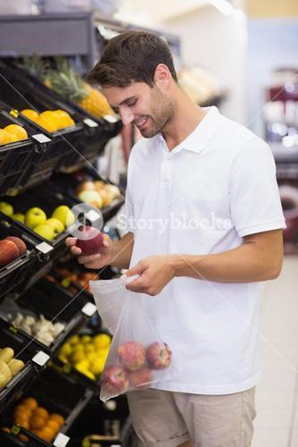 Smiling handsome buying a fruits