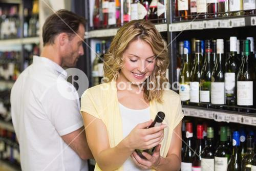 Smiling pretty blonde woman looking at wine bottle