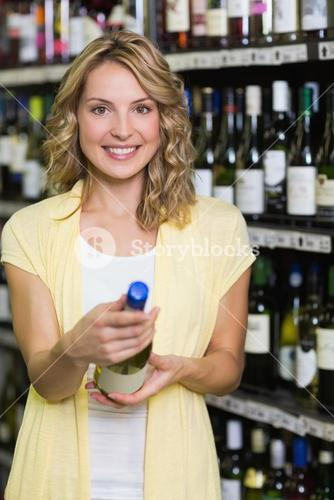 Portrait of a smiling pretty blonde woman looking at wine bottle