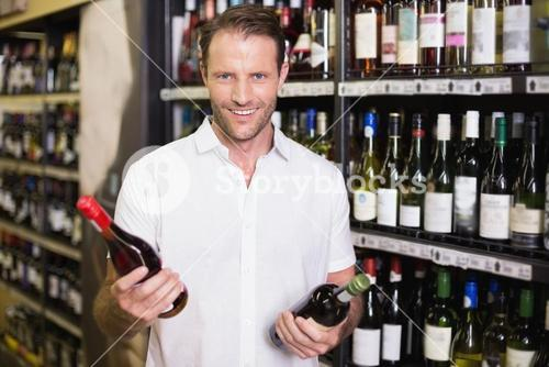 Portrait of a smiling handsome showing a wine bottle