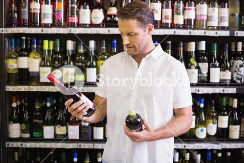 A handsome looking at wine bottle