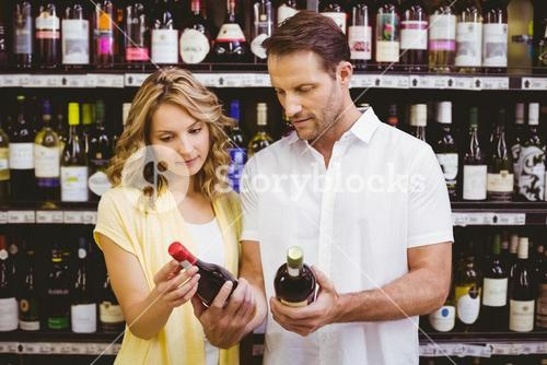 Casual couple looking at wine bottle