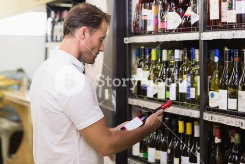 Handsome looking at wine bottle