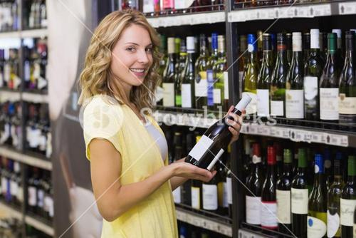 Portrait of a smiling pretty blonde woman having a wine bottle in her hands