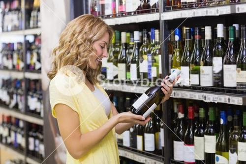 Smiling pretty blonde woman looking at a wine bottle