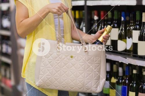 Pretty woman putting a champagne bottle in her bag