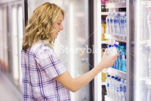 Smiling blonde woman taking a water bottle