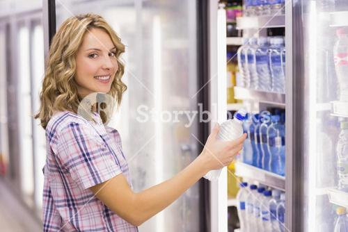 Portrait of a smiling pretty blonde woman taking a water bottle