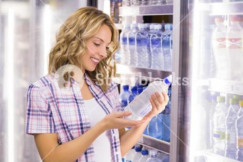 Smiling pretty blonde woman looking at a water bottle