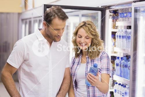 Smiling cacual couple looking at water bottle