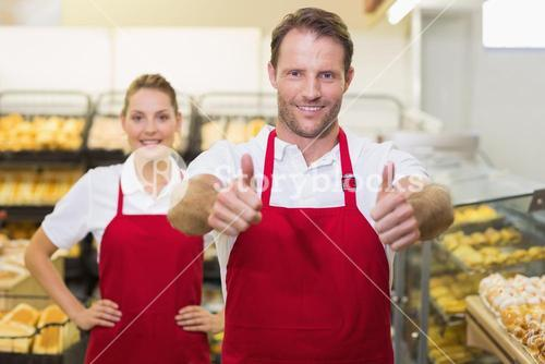 Portrait of smiling two bakers with thumb up