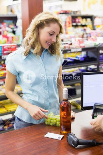 Smiling woman at cash register paying with credit card