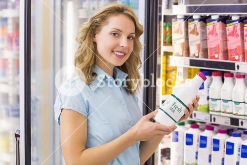 Portrait of a smiling woman having on her hands a milk bottle