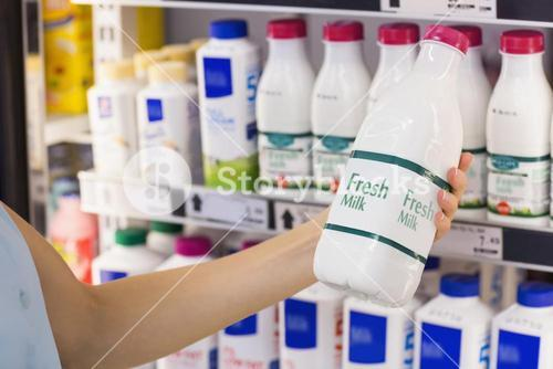 A woman having on her hands a fresh milk bottle