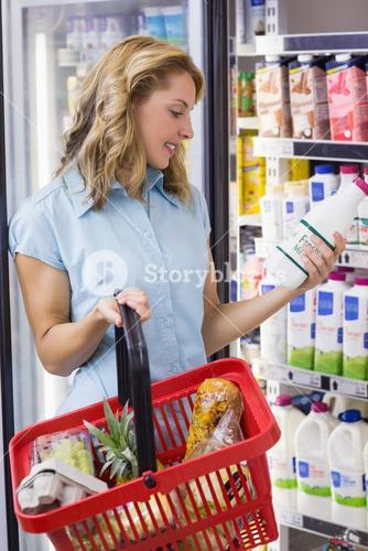 Smiling woman having on her hands a fresh milk bottle