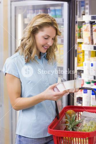 Smiling woman looking at a yogurt on her hands