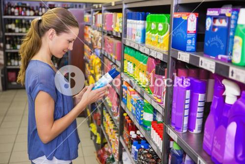 Thoughtful pretty brunette looking at product in shelf