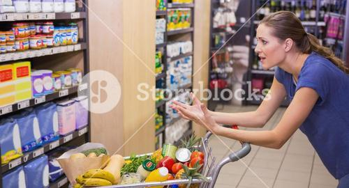 Surprised woman looking at product on shelf