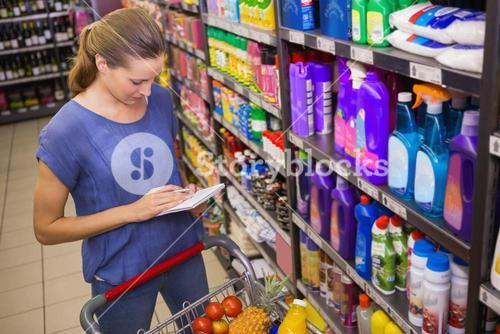 Pretty woman looking at her grocery list