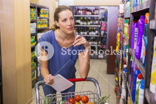Pretty woman looking at product on shelf and holding grocery list