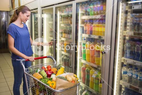 Pretty woman looking at camera and taking product on fridge