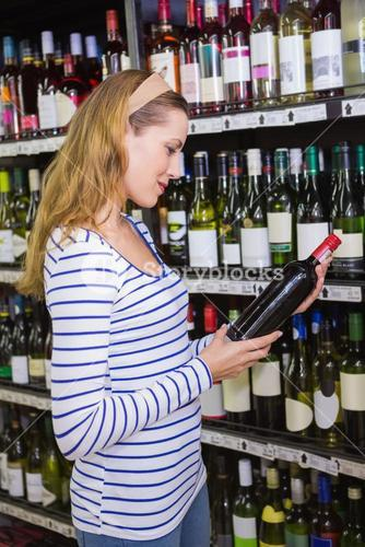 Pretty blonde woman holding a bottle of red wine