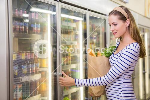 Pretty woman taking product on fridge