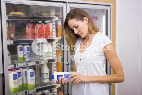Pretty woman looking at bottle of milk