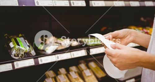 A woman looking at her grocery list