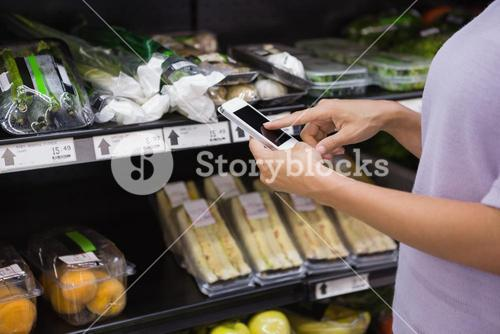 Woman reading her shopping list on smartphone