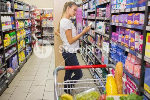 Smiling woman taking lotion in the shelf of aisle