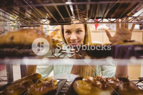 Portrait of a woman looking at new plates with pastries