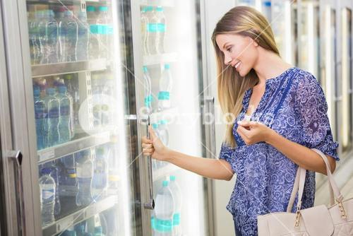 A pretty smiling blonde woman buying frozen products