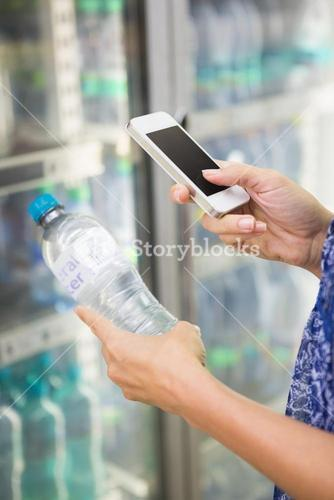 Woman comparing the price of a bottle of water with her phone