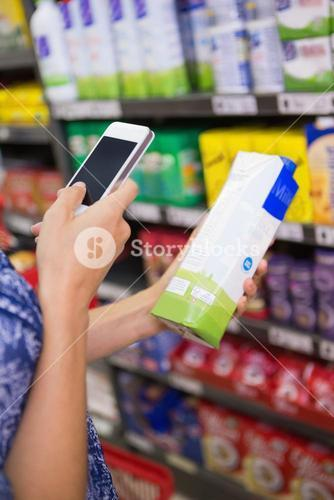 Woman comparing the price of a carton of milk with her phone
