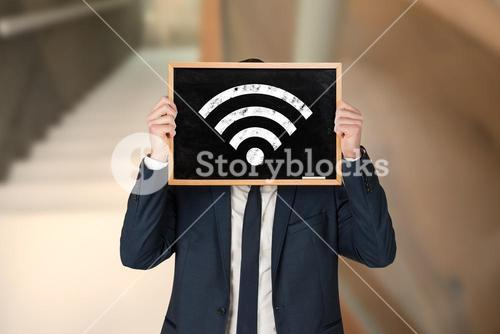 Composite image of businessman holding board